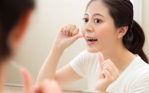 woman flossing teeth - how often should I brush my teeth
